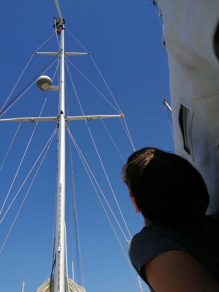 Pati looking up the mast to watch Dave