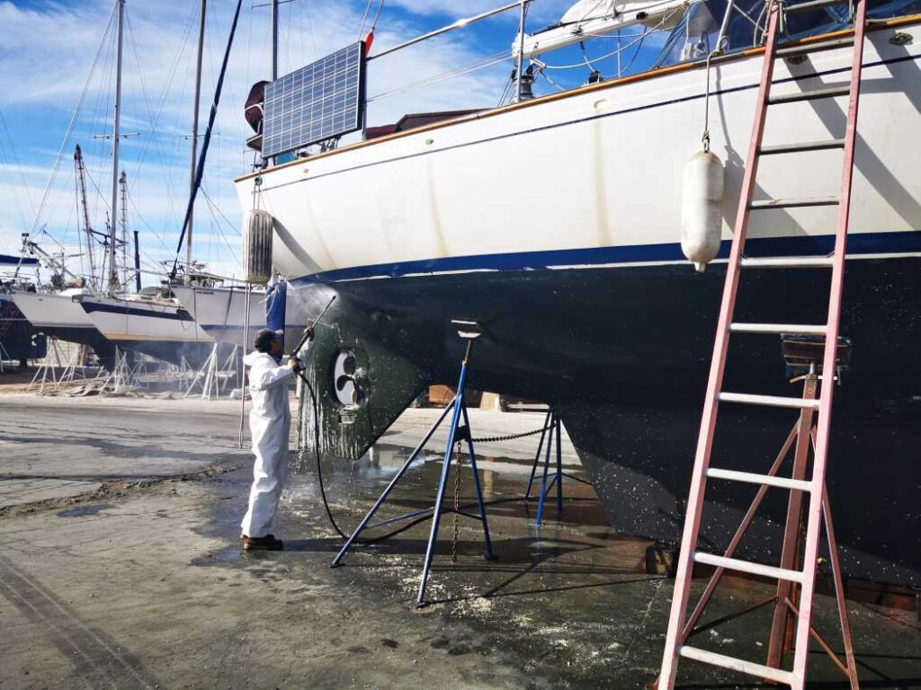 A worker pressure washing the hull of Milagros