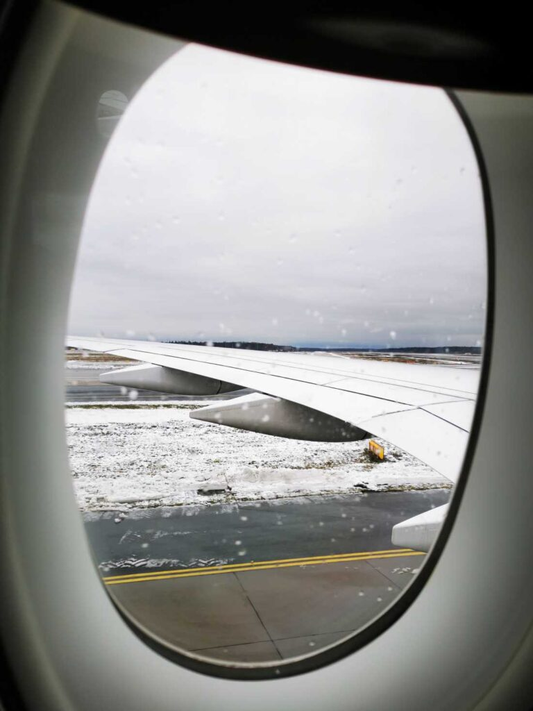 Looking out the window of the airplane onto a snowy Zurich Airport