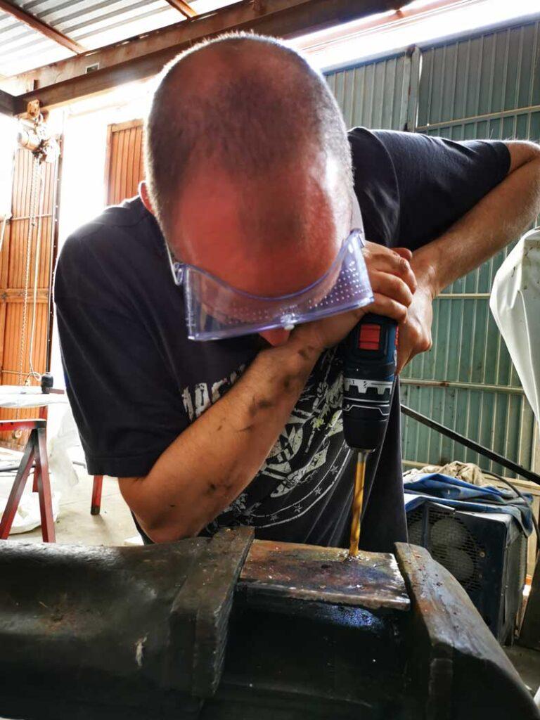 Dave perce des trous dans la plaque métallique