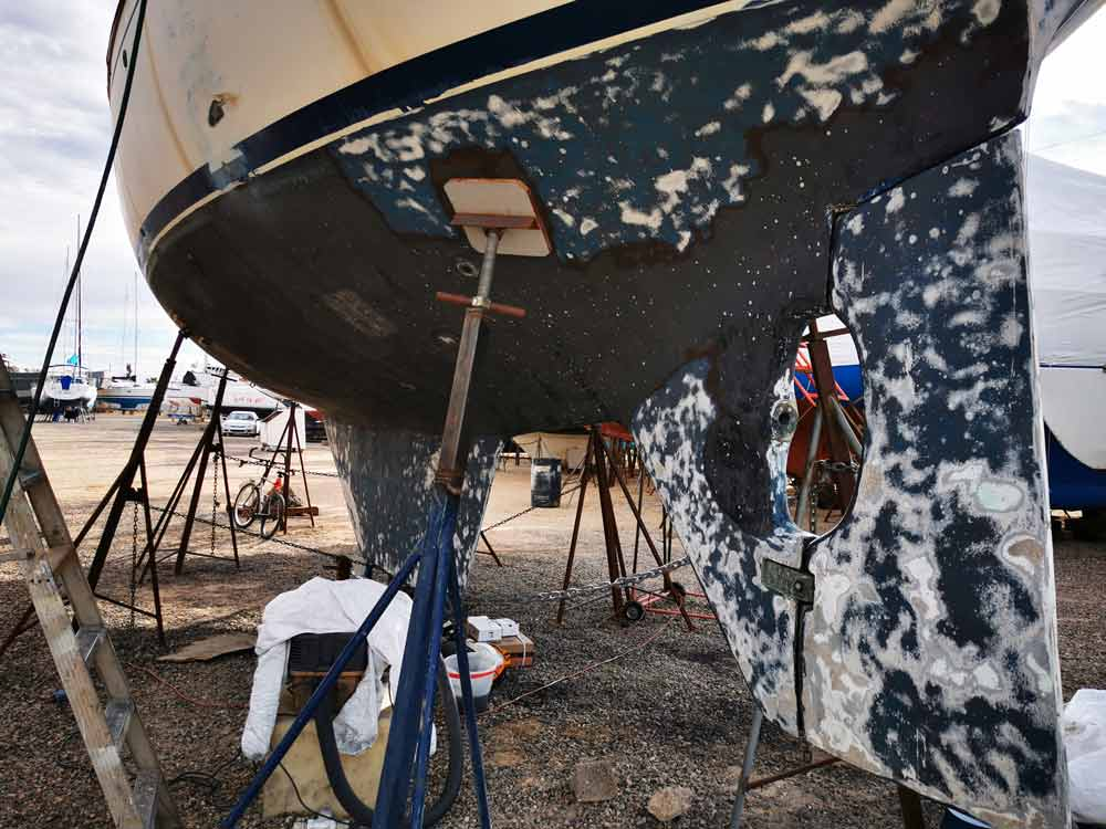 Sanding the hull of a Kelly Peterson 44 bluewater cruiser sailboat.