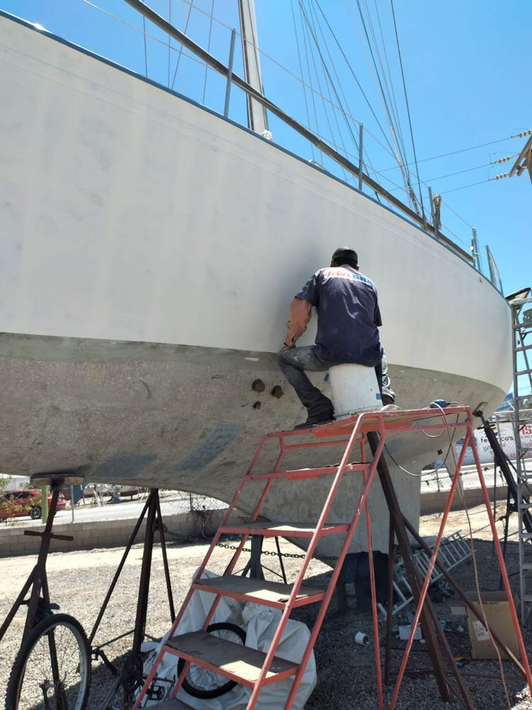 Boatyard worker sanding the primer of a sailboat